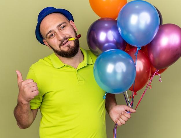 Zadowolony młody facet w imprezowym kapeluszu, trzymający balony dmuchające w gwizdek pokazujący kciuk na białym tle na oliwkowozielonej ścianie