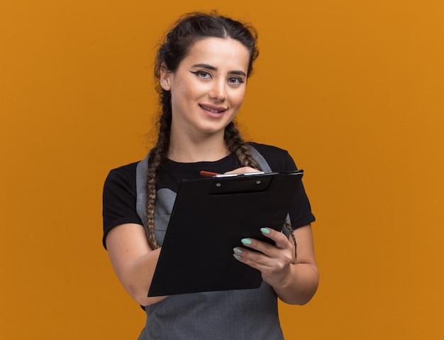 Zadowolony młody fryzjer żeński w mundurze pisze coś w schowku na białym tle na pomarańczowej ścianie