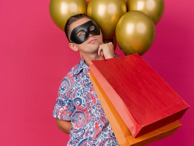 Zadowolony młody imprezowicz patrząc na kamerę w masce na oczy maskaradowej stojącej przed balonami, trzymając torby z prezentami, kładąc rękę na brodzie na białym tle na różowym tle