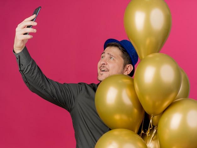 Zadowolony młody imprezowicz w niebieskim kapeluszu stojący wśród balonów i zrób selfie na różowo