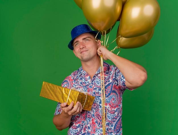 Zadowolony młody imprezowicz w niebieskim kapeluszu, trzymając balony z pudełkiem na białym tle na zielono