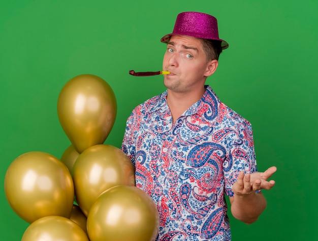 Zadowolony młody imprezowicz w różowym kapeluszu stojący obok balonów dmuchanie imprezę dmuchanie rozłożoną ręką na białym tle na zielono