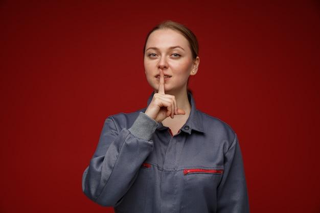 Zadowolony młody inżynier blond kobieta ubrana w mundur robi gest ciszy