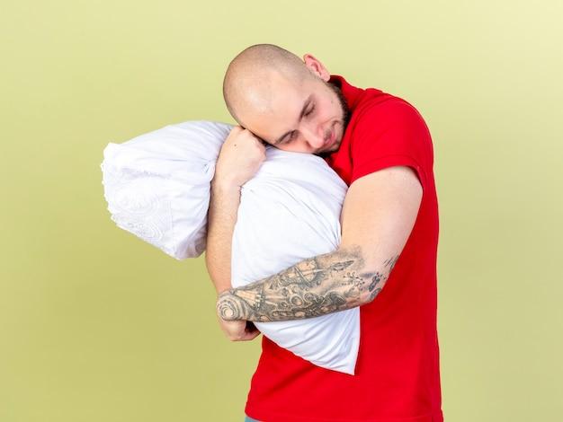 Zadowolony młody kaukaski chory mężczyzna przytula i kładzie głowę na poduszce odizolowanej na oliwkowej ścianie z miejsca na kopię