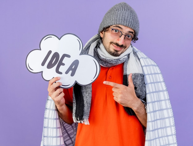 Zadowolony młody kaukaski chory mężczyzna w okularach czapka zimowa i szalik owinięty w kratę, trzymając i wskazujący na bańkę pomysłów patrząc na kamerę odizolowaną na fioletowym tle