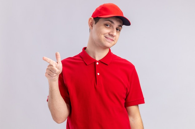 Zadowolony młody kaukaski dostawca w czerwonej koszuli, wskazując na bok