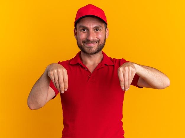 Zadowolony młody kaukaski dostawca w czerwonym mundurze i czapce patrzący na kamerę udaje, że trzyma coś odizolowanego na pomarańczowej ścianie