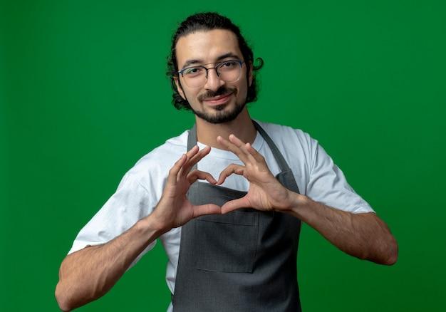 Zadowolony młody kaukaski fryzjer męski w mundurze i okularach robi znak serca na białym tle na zielonym tle