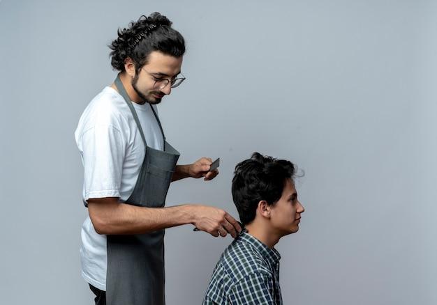 Zadowolony młody kaukaski fryzjer męski w okularach i falistej opasce do włosów w mundurze, stojący w widoku profilu, robi fryzurę dla swojego młodego klienta na białym tle z miejsca na kopię