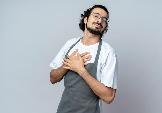 Zadowolony młody kaukaski fryzjer męski w okularach i falującej opasce do włosów w mundurze kładzie ręce na klatce piersiowej z zamkniętymi oczami na białym tle z miejsca na kopię