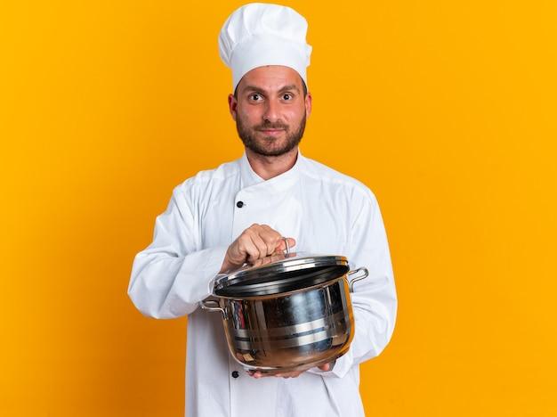 Zadowolony młody kaukaski kucharz w mundurze szefa kuchni i czapce trzymającej garnek chwytający pokrywkę garnka