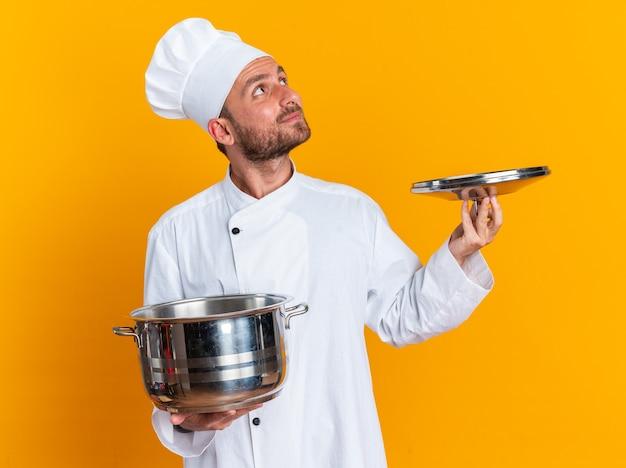 Zadowolony młody kaukaski kucharz w mundurze szefa kuchni i czapce trzymającej garnek i pokrywkę garnka patrząc w górę