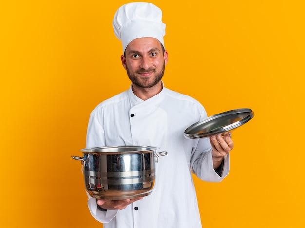 Zadowolony młody kaukaski kucharz w mundurze szefa kuchni i czapce trzymającej pokrywkę garnka i garnek patrzący na kamerę odizolowaną na pomarańczowej ścianie