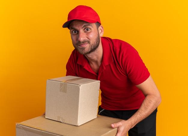 Zadowolony młody kaukaski mężczyzna dostawy w czerwonym mundurze i czapce pochyla się, trzymając ręce na kartonie, patrząc na kamerę odizolowaną na pomarańczowej ścianie