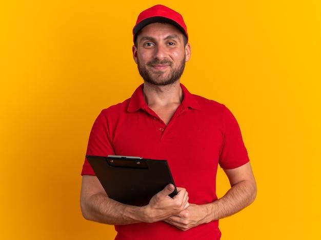 Zadowolony młody kaukaski mężczyzna dostawy w czerwonym mundurze i czapce trzymającej schowek, patrząc na kamerę odizolowaną na pomarańczowej ścianie