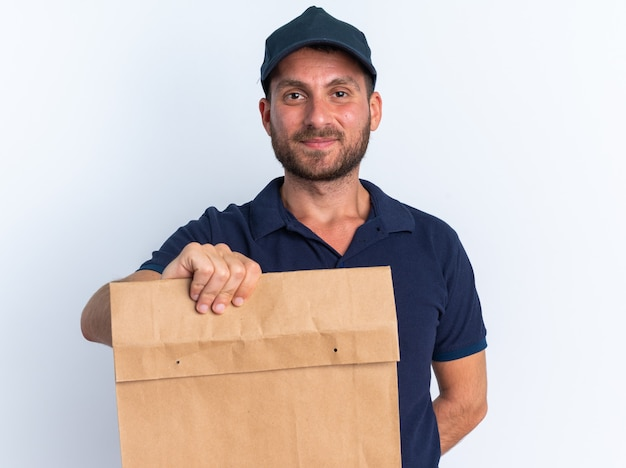 Zadowolony młody kaukaski mężczyzna dostawy w niebieskim mundurze i czapce trzymającej rękę za plecami, wyciągając papierowy pakiet w kierunku kamery, patrząc na kamerę na białym tle na białej ścianie