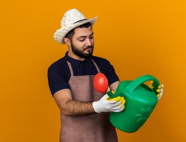 Zadowolony młody kaukaski ogrodnik mężczyzna ubrany w kapelusz ogrodniczy i rękawiczki, trzymając i patrząc na konewkę na białym tle na pomarańczowej ścianie z miejsca na kopię