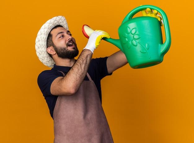 Zadowolony młody kaukaski ogrodnik mężczyzna w kapeluszu ogrodniczym udając, że pije z konewki na białym tle na pomarańczowej ścianie z miejsca na kopię