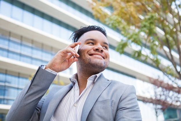Zadowolony młody kierownik cieszy się rozmowę telefoniczną