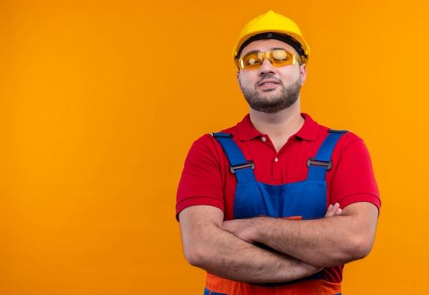 Zadowolony młody konstruktor w mundurze konstrukcyjnym i kasku ze skrzyżowanymi rękami na piersi wygląda pewnie