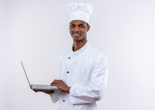 Zadowolony młody kucharz afroamerykański w mundurze szefa kuchni trzyma laptopa i patrzy na kamerę na na białym tle z miejsca na kopię