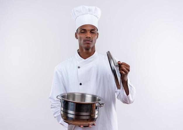 Zadowolony młody kucharz afroamerykański w mundurze szefa kuchni trzyma rondel z zamkniętymi oczami na odosobnionym białym tle z miejsca na kopię