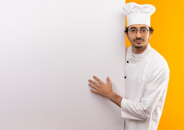 Zadowolony młody kucharz mężczyzna ubrany w mundur szefa kuchni i okulary trzyma białą ścianę