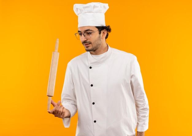 Zadowolony młody kucharz mężczyzna ubrany w mundur szefa kuchni i okulary trzymając wałek do ciasta na palcu na białym tle na żółtej ścianie