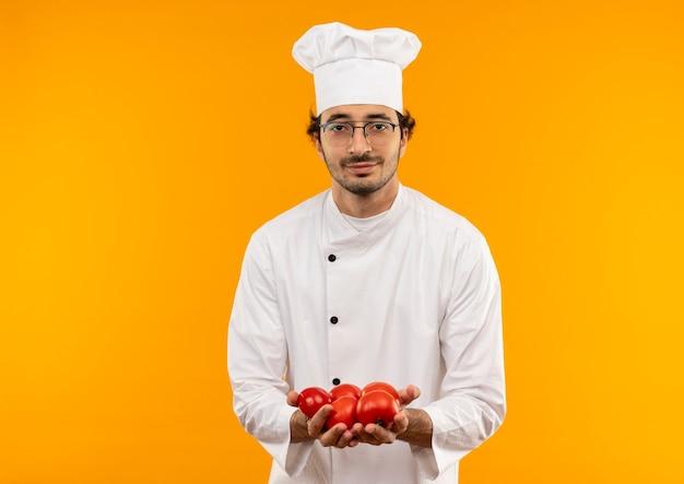 Zadowolony młody kucharz mężczyzna w mundurze szefa kuchni i okularach trzyma pomidora na białym tle na żółtej ścianie