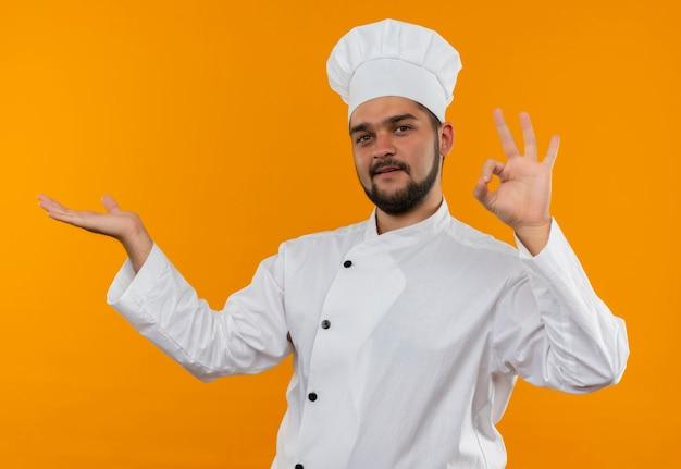Zadowolony młody kucharz mężczyzna w mundurze szefa kuchni pokazuje pustą rękę i robi znak ok na białym tle na pomarańczowej przestrzeni