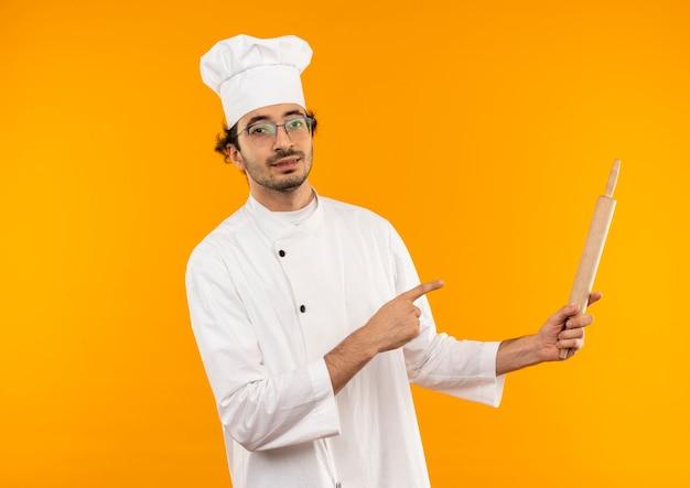 Zadowolony młody kucharz w mundurze szefa kuchni i okularach trzyma i wskazuje na wałek do ciasta na białym tle na żółtej ścianie