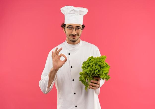Zadowolony młody kucharz w mundurze szefa kuchni i okularach trzyma sałatkę i pokazuje gest okey na różowej ścianie