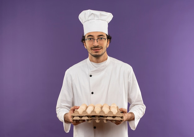 Zadowolony młody kucharz w mundurze szefa kuchni i okularach, trzymając partię jaj na fioletowo