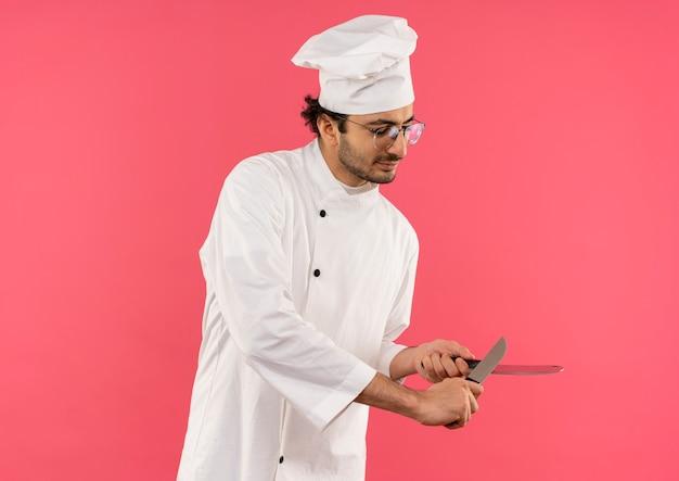 Zadowolony młody kucharz w mundurze szefa kuchni i okularach zaostrzy nóż tasakiem na różowej ścianie