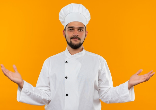 Zadowolony młody kucharz w mundurze szefa kuchni, pokazujący puste ręce i patrząc na odizolowany w pomarańczowej przestrzeni