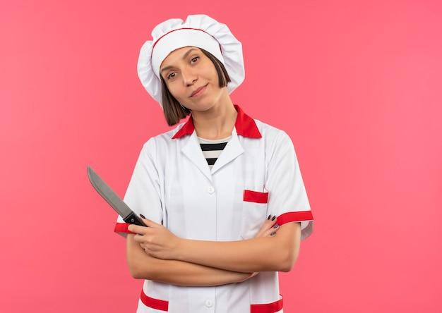 Zadowolony młody kucharz w mundurze szefa kuchni stojący z zamkniętą posturą i trzymając nóż na białym tle na różowej ścianie