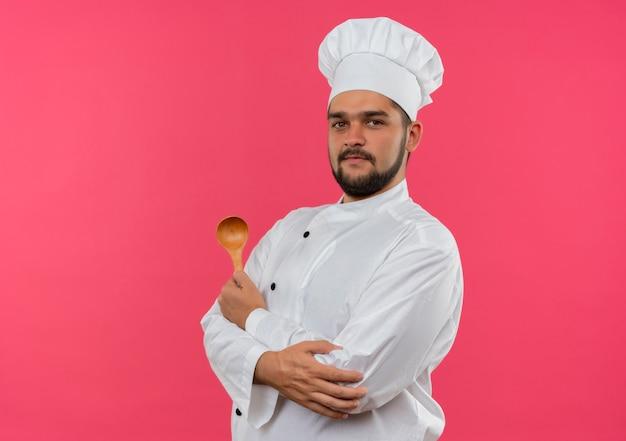 Zadowolony młody kucharz w mundurze szefa kuchni, trzymając łyżkę i kładąc rękę na łokciu na białym tle na różowej przestrzeni