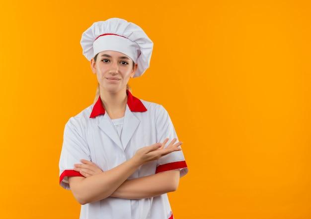 Zadowolony młody ładny kucharz w mundurze szefa kuchni, stojący z zamkniętą posturą i pokazujący pustą dłoń odizolowaną na pomarańczowej przestrzeni