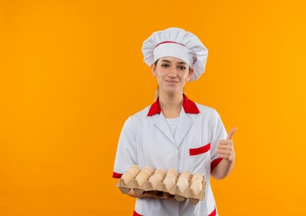Zadowolony młody ładny kucharz w mundurze szefa kuchni, trzymając karton jaj i pokazując kciuk do góry na białym tle na pomarańczowej przestrzeni