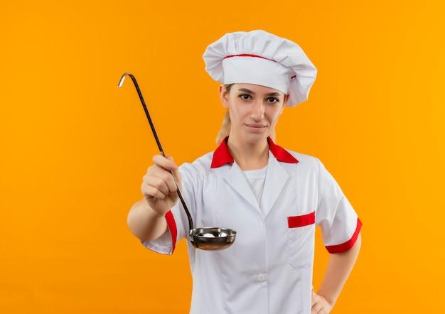 Zadowolony młody ładny kucharz w mundurze szefa kuchni wyciągający chochlę z ręką na talii odizolowany na pomarańczowej przestrzeni