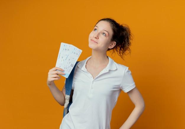 Zadowolony młody ładny studentka na sobie plecak trzymając bilety lotnicze patrząc na białym tle na pomarańczowym tle z miejsca na kopię