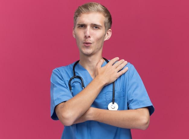 Zadowolony młody lekarz mężczyzna ubrany w mundur lekarza ze stetoskopem, kładąc rękę na ramieniu na białym tle na różowej ścianie