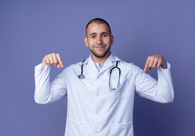 Zadowolony młody lekarz mężczyzna ubrany w szlafrok medyczny i stetoskop na szyi, wskazując w dół na białym tle na fioletowej ścianie