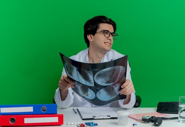 Zadowolony młody lekarz płci męskiej ubrany w szlafrok medyczny i stetoskop w okularach siedzi przy biurku z narzędziami medycznymi trzymającymi zdjęcie rentgenowskie patrząc na bok na białym tle