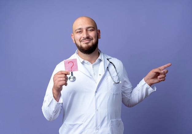 Zadowolony młody łysy lekarz mężczyzna ubrany w szatę medyczną i stetoskop, trzymający papierowy znak zapytania i punkty z boku