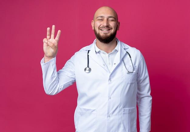 Zadowolony młody łysy lekarz mężczyzna ubrany w szlafrok i stetoskop pokazujący trzy na białym tle na różowej ścianie