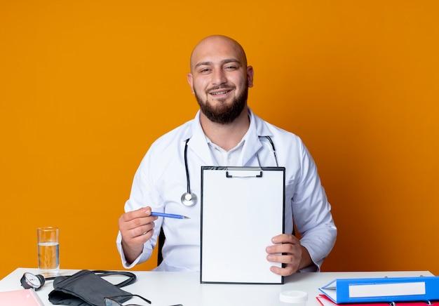 Zadowolony młody łysy lekarz mężczyzna ubrany w szlafrok medyczny i stetoskop siedzi przy biurku z narzędziami medycznymi, trzymając i wskazuje piórem w schowku na białym tle na pomarańczowym tle