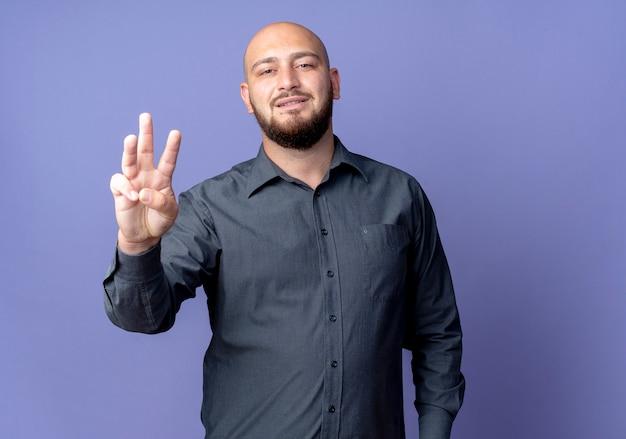 Zadowolony młody łysy mężczyzna call center pokazano trzy z ręką na białym tle na fioletowym tle z miejsca na kopię