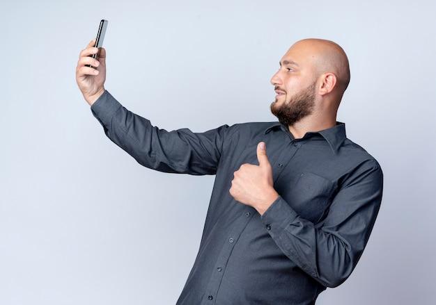 Zadowolony młody łysy mężczyzna call center pokazując kciuk w górę i biorąc selfie na białym tle