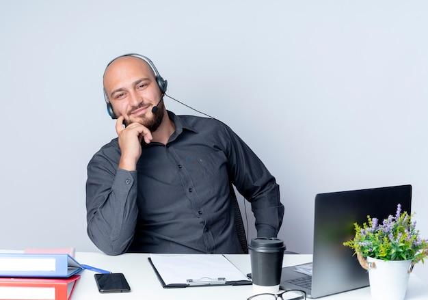 Zadowolony młody łysy mężczyzna call center sobie zestaw słuchawkowy siedzi przy biurku z narzędzi pracy kładąc palec na policzku na białym tle